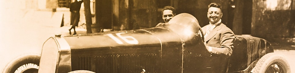 Black and white photo of Enzo Ferrari sitting in one of the first Ferrari cars