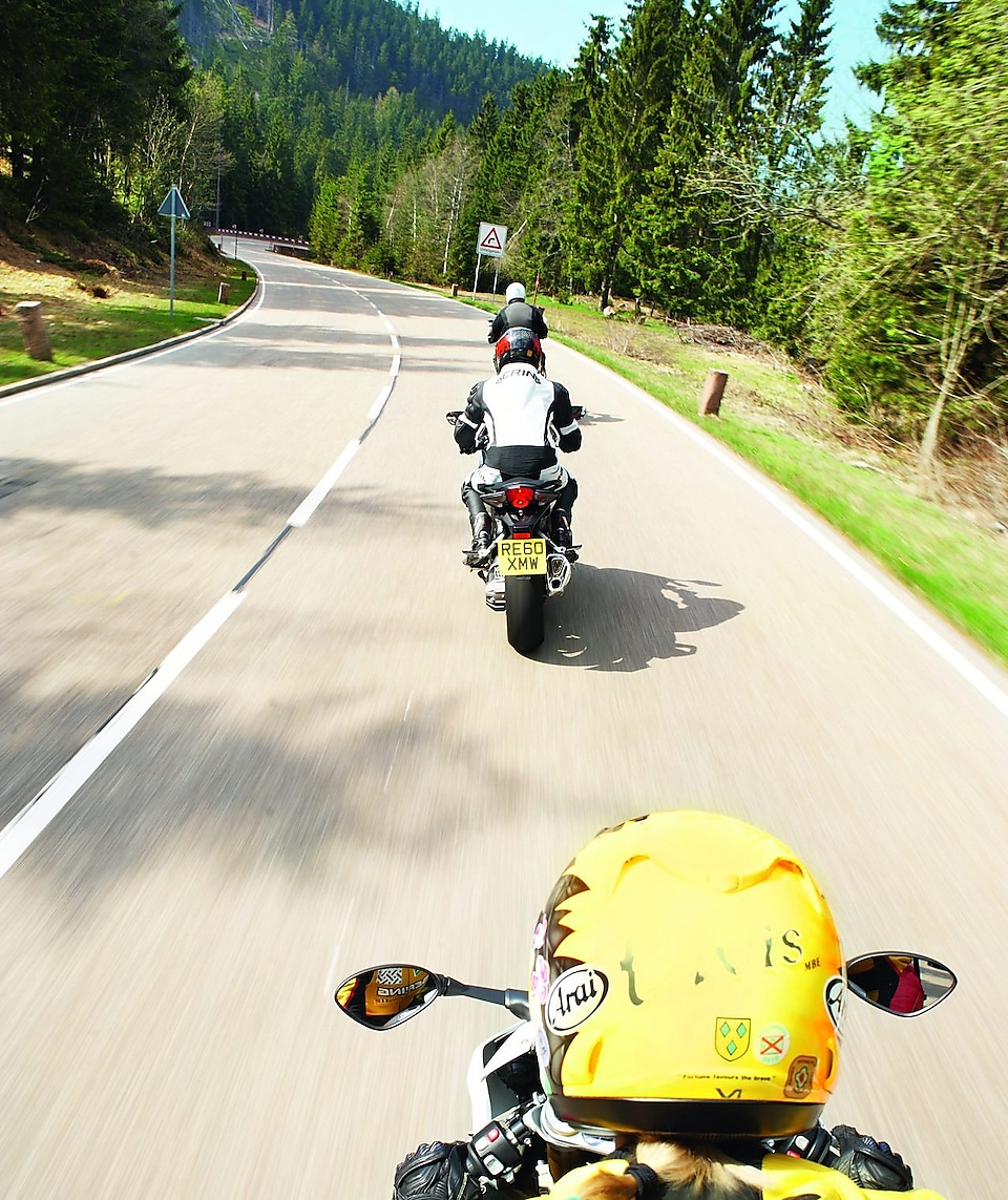 Three motorbikes being ridden along a mountain road