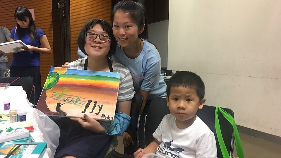 Student with special educational needs held her painting and took photo with parent and volunteer.