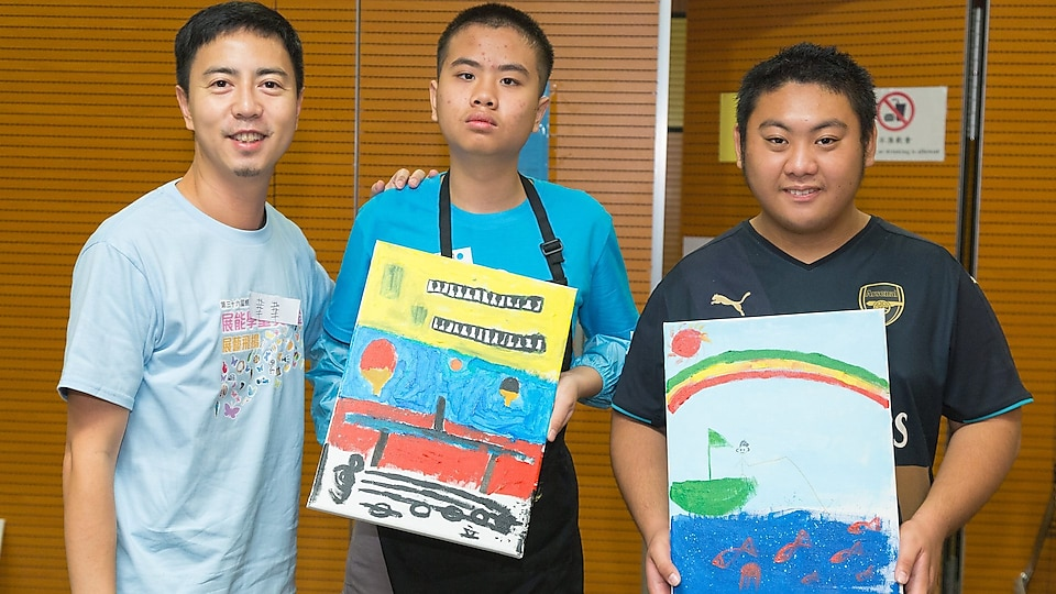 Students with special educational needs and volunteer took photo with paintings.