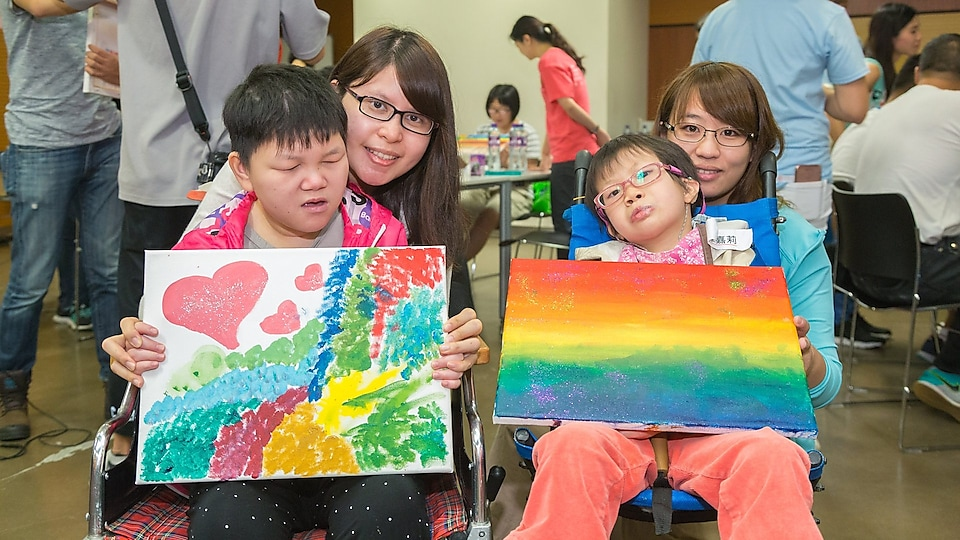 Students with special educational needs and teacher took photo with their paintings.
